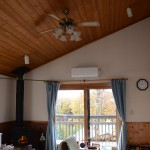 リビング北側から南方向を撮影。東南側に薪ストーブ。正面のエアコンは昨年設置したもの。天井は天然木を使用。