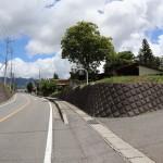 西側舗装公道の北方向(小淵沢駅方向)を撮影。右側石垣部分が物件への入口。