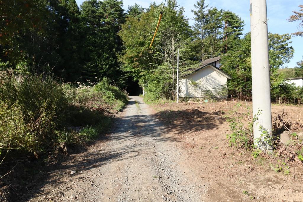 物件西側幅員約3m公道の南側から北方向を撮影。物件は道路右側。道路突き当りを右へ約260mで石堂信号。