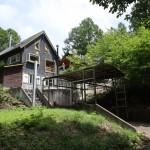 物件南西側から撮影。正面が角ログハウス。角ログハウスから階段を下りた場所が屋根付きカーポート。物件は高台に立地。
