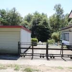 敷地玄関側を北側から撮影。左にガレージ、正面が駐車スペースのコンクリート舗装部分、その奥が菜園スペース。