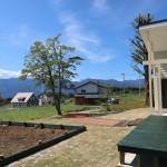 建物東南側から南西方向を撮影。手前がウッドデッキ。左手の木枠で囲まれた部分が菜園。正面アプローチの先に南アルプスの眺望。