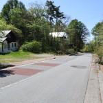 物件西側公道(牧場通り)の北側から南方向を撮影。物件入口は道路左側。