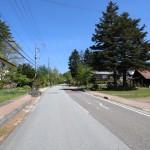 物件西側に接面する公道(牧場通り)の北方向を撮影。物件への入口は道路右側樅の木の手前。