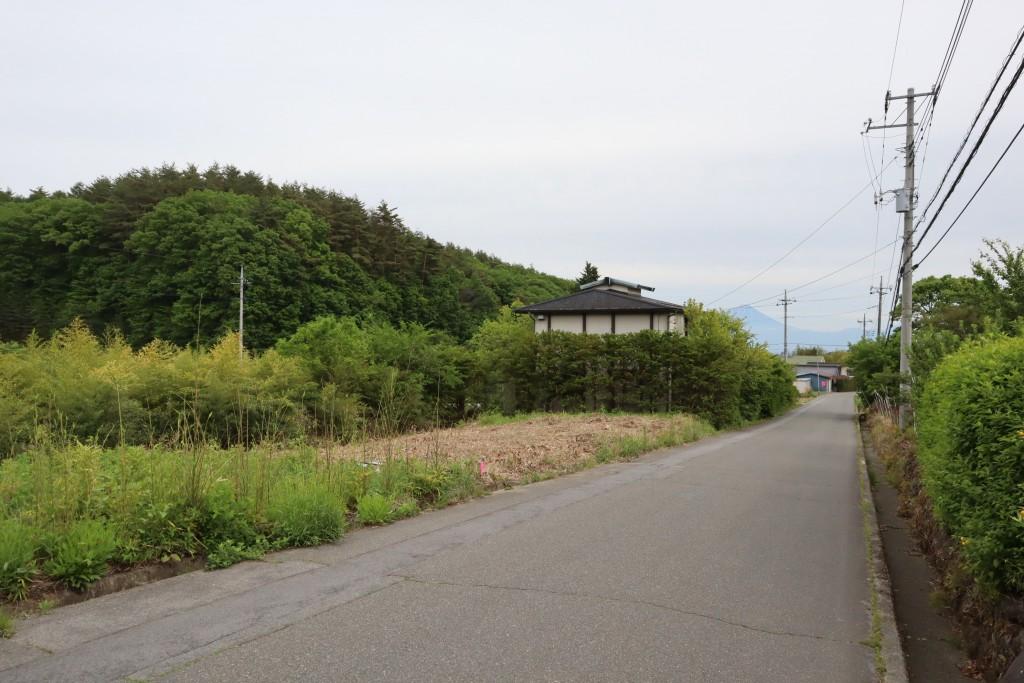 物件に接面する公道の北側から南方向を撮影。物件は道路左側の草を刈った部分。南側隣地に建つ家の右上に富士山の眺望あり。